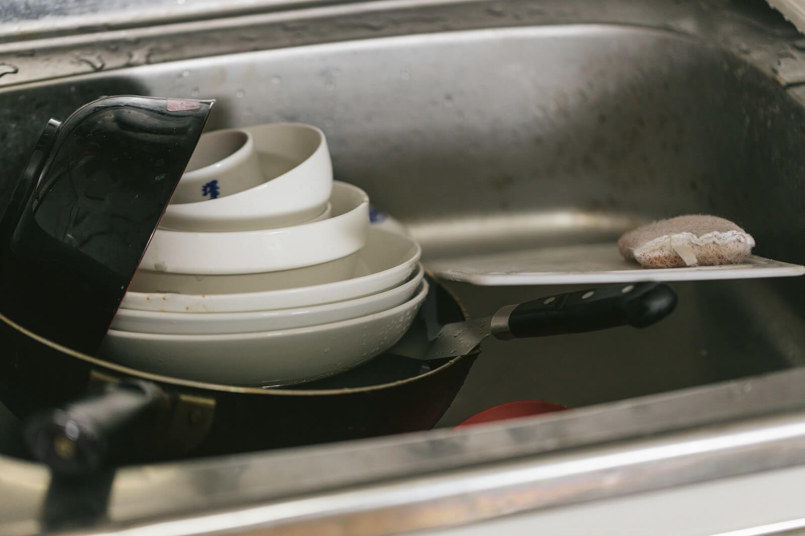 シンクに溜まった食器の画像
